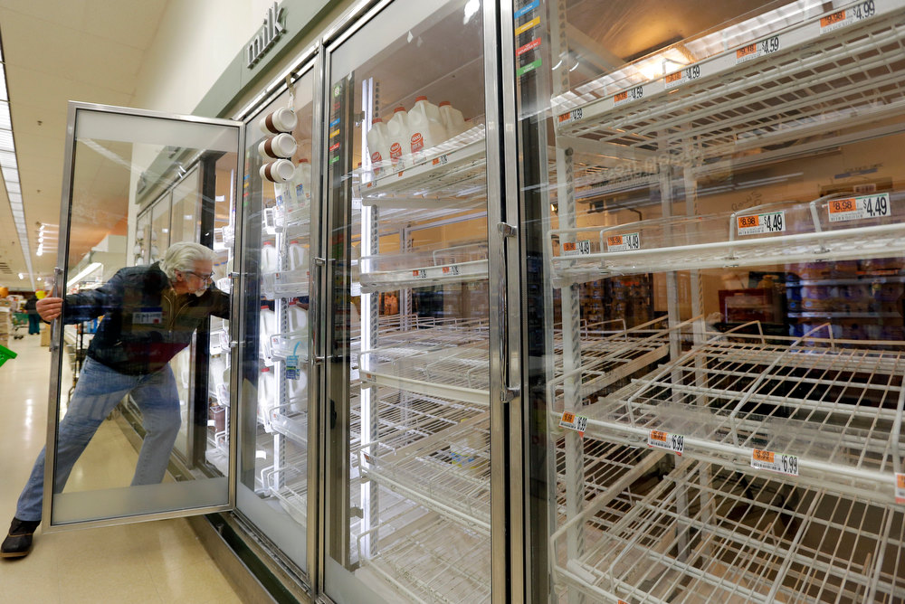 . Jack Percoco of Cambridge, Mass. reaches into depleted shelves for milk at a supermarket in Somerville, Mass., Friday, Feb. 8, 2013. A major winter storm is heading toward the U.S. Northeast with up to 2 feet of snow expected for a Boston-area region that has seen mostly bare ground this winter. (AP Photo/Elise Amendola)