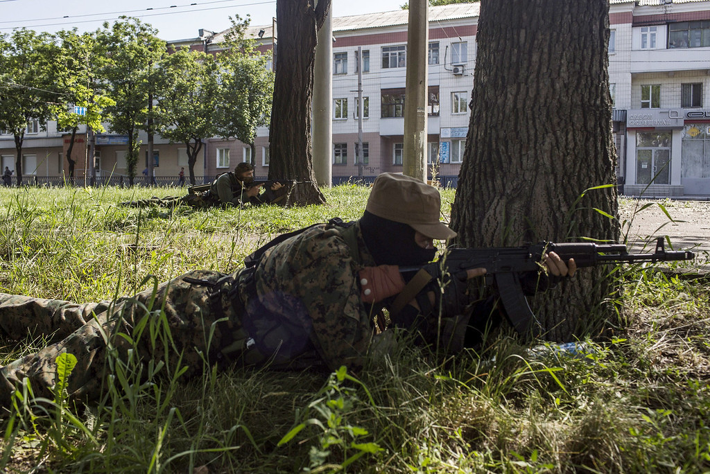 . Pro-Russian fighters take position behind trees during clashes against Ukrainian forces near the airport in Donetsk on May 26, 2014. The battle at the airport in the main eastern rebel-held city of Donetsk on Monday marked a dramatic new phase in the government\'s offensive against pro-Russian separatists. The fierce confrontation erupted after Ukrainian oligarch Petro Poroshenko, who claimed victory in Sunday\'s crucial presidential election, vowed he would not let the separatists turn the east into another Somalia.  FABIO BUCCIARELLI/AFP/Getty Images
