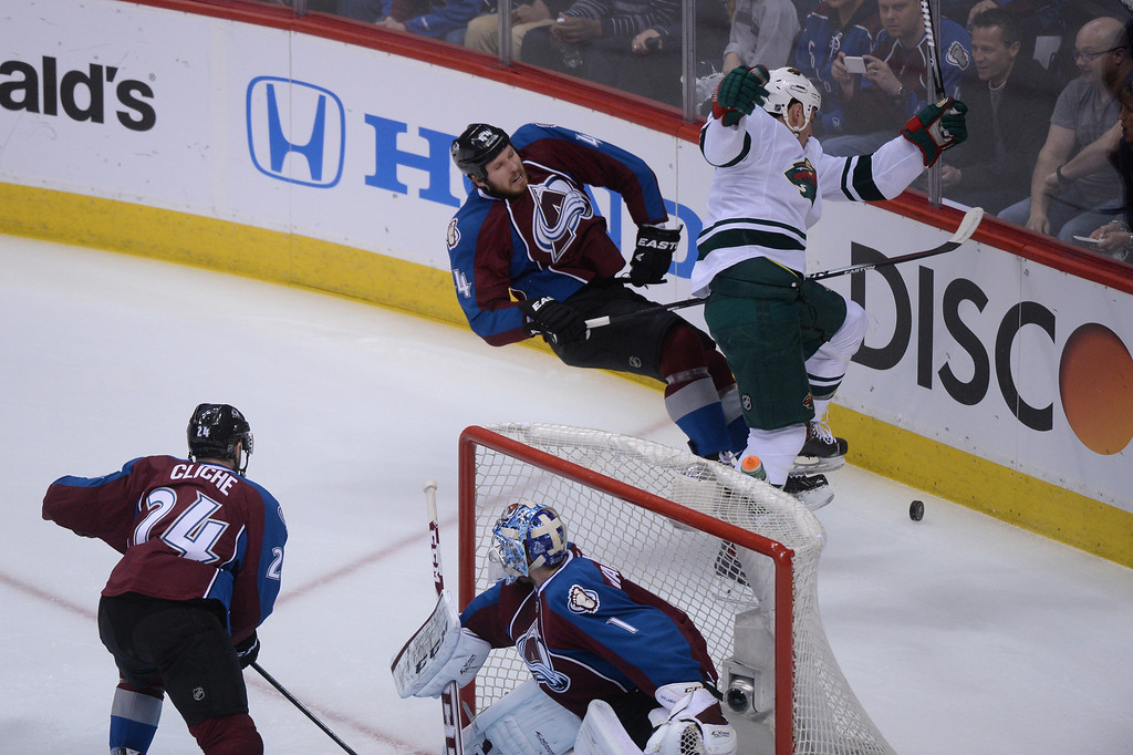 . Ryan Wilson (44) of the Colorado Avalanche battles Cody McCormick (8) of the Minnesota Wild for control of the puck during the first period of action.  (Photo by Karl Gehring/The Denver Post)