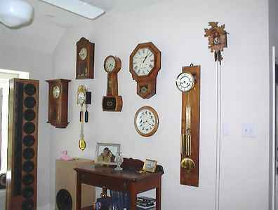 """Gameroom - Wall of clocks. L to R: Gustav Becker box clock, small box clock of unknown origin, (below) Swiss double weight with bell chime, US Lighthouse clock, Ansonia schoolhouse advertising clock with the words """"Sam Bowes New York"""" painted on the face, (below) quartz clock with bird calls on the hour, Kenninger double weight movement on walnut board, cuckoo clock. The early 20th century walnut server below is from a farmhouse near Athens, GA."""