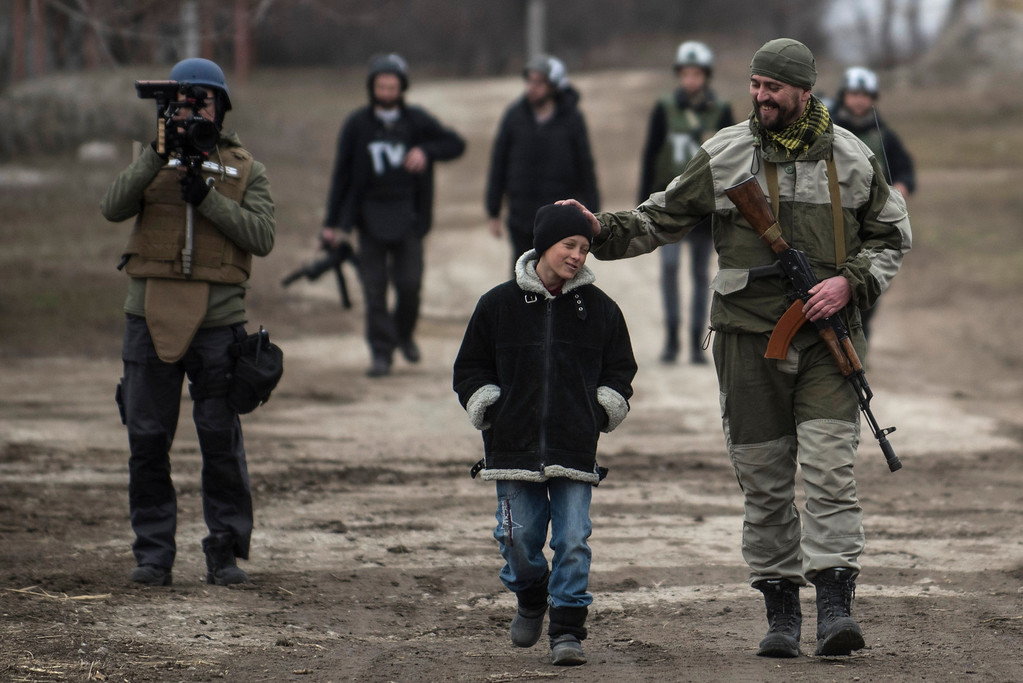 . A Ukrainian serviceman speaks with a schoolboy in the village of Chermalyk, eastern Ukraine, Thursday, Feb. 26, 2015. In a long-awaited development, Ukrainian forces and separatist fighters both announced Thursday they are moving heavy weapons from the front line in eastern Ukraine. (AP Photo/Evgeniy Maloletka)
