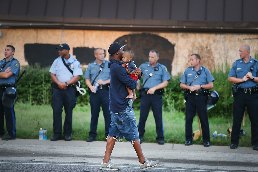 . A man carries his child past a row of police tasked with keeping the peace as demonstration to protest the killing of teenager Michael Brown on August 17, 2014 in Ferguson, Missouri.   Despite the Brown family\'s continued call for peaceful demonstrations, violent protests have erupted nearly every night in Ferguson since his death. (Photo by Scott Olson/Getty Images)