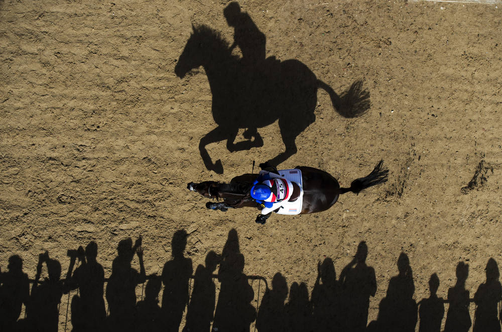 . Thailand\'s Nina Lamsan Ligon riding Butts Leon rides past spectators as she competes in the Cross Country phase of the Eventing competition of the 2012 London Olympics at the Equestrian venue in Greenwich Park, London, July 30, 2012. AFP PHOTO / ADRIAN  DENNIS/AFP/Getty Images
