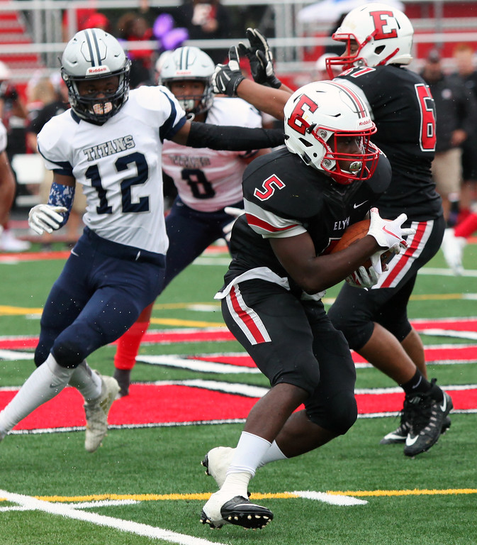 . Randy Meyers - The Morning Journal<br> Elyria running back Jaheim Atkinson runs behind a block for a short gain against the Lorain defense on Sept. 8.
