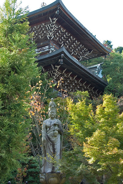 Buddha statue with Daisho-in Temple  in the background at Miyajima, Japan