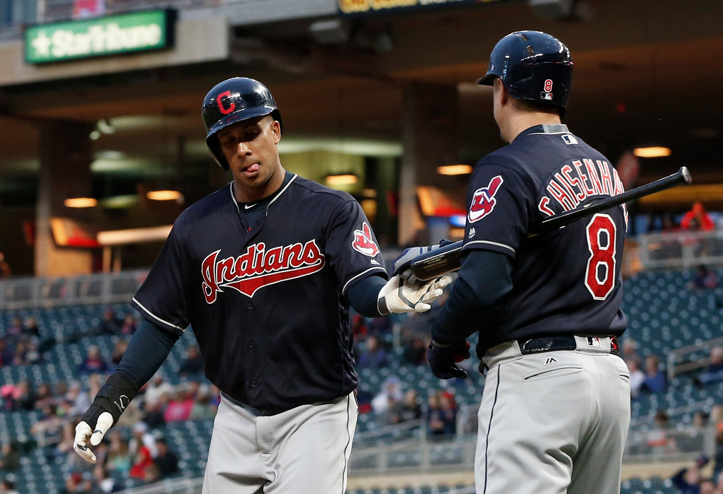 . Cleveland Indians\' Michael Brantley, left, is congratulated by Lonnie Chisenhall after scoring against the Minnesota Twins during the first inning of a baseball game Tuesday, April 18, 2017, in Minneapolis. (AP Photo/Jim Mone)
