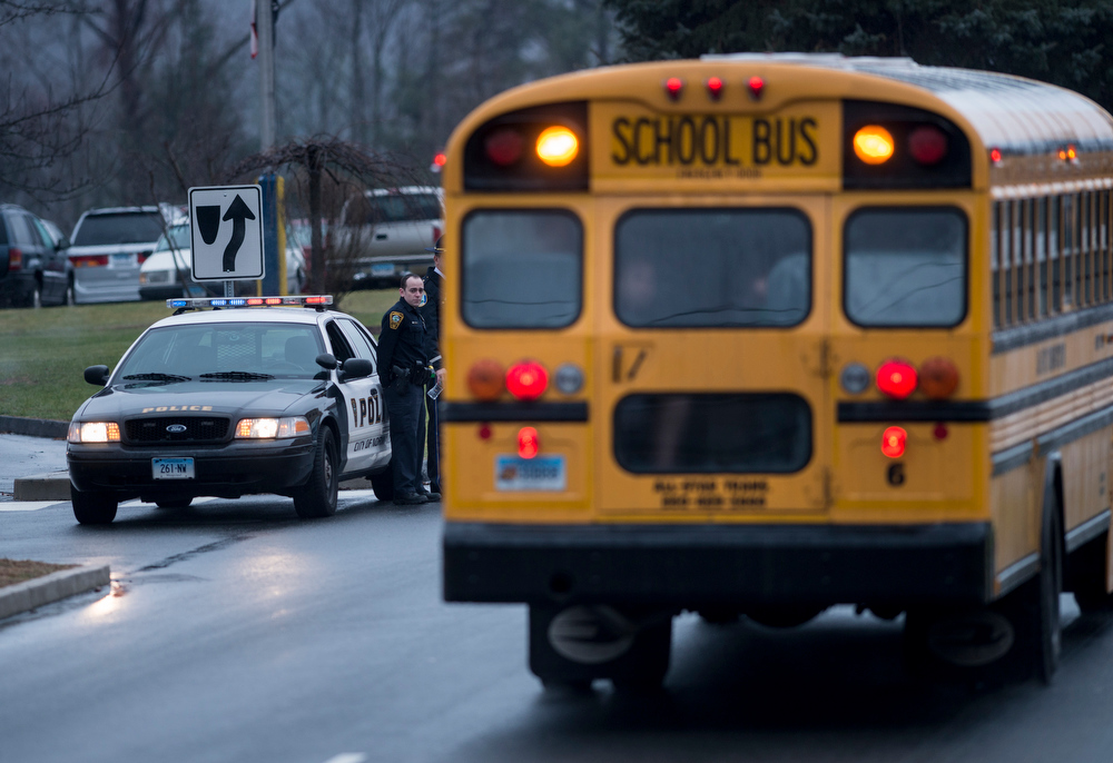 . Police watch as school bus takes students to Newtown High School December 18, 2012 in Newtown, Connecticut. Students in Newtown, excluding Sandy Hook Elementary School, return to school for the first time since last Friday\'s shooting at Sandy Hook which took the live of 20 students and 6 adults.  BRENDAN SMIALOWSKI/AFP/Getty Images
