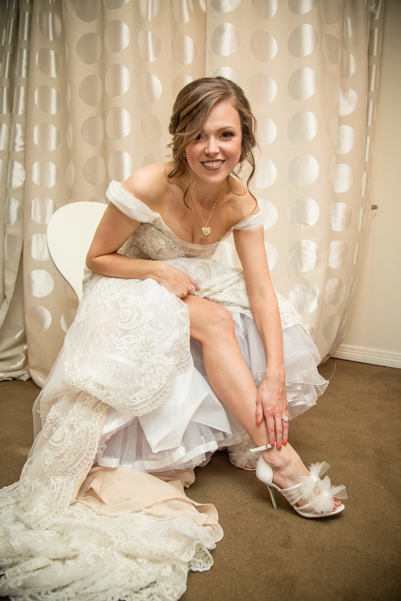 A bride adjusting the strap of her high heeled shoes as she finishes getting ready for hre wedding