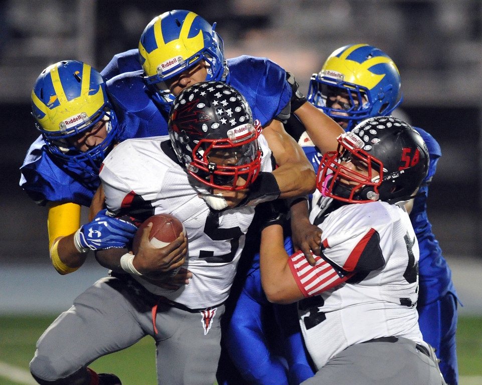 . Pomona quarterback Darreon Lockett (#5) is sacked by San Dimas defenders in their Valley Vista League football game at San Dimas High School on November 8, 2013. San Dimas defeated Pomona 49-6. (San Gabriel Valley Tribune/Staff Photo by Keith Durflinger)