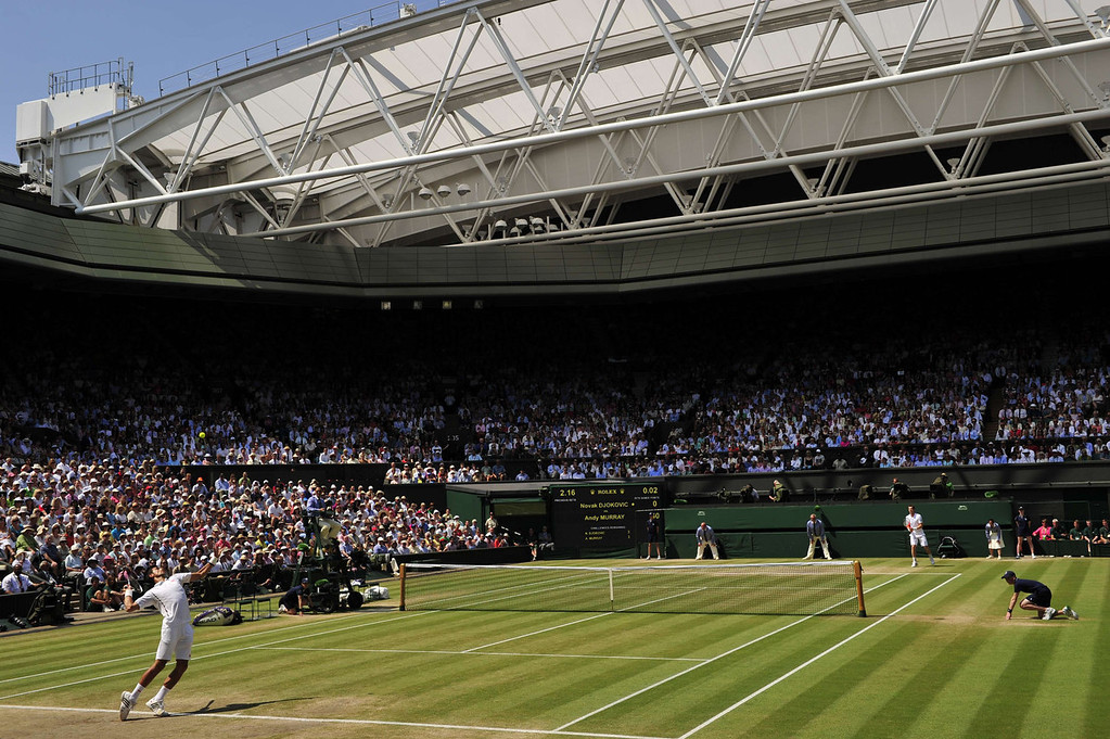 . Serbia\'s Novak Djokovic (L) serves against Britain\'s Andy Murray (R) during the men\'s singles final on day thirteen of the 2013 Wimbledon Championships tennis tournament at the All England Club in Wimbledon, southwest London, on July 7, 2013. GLYN KIRK/AFP/Getty Images
