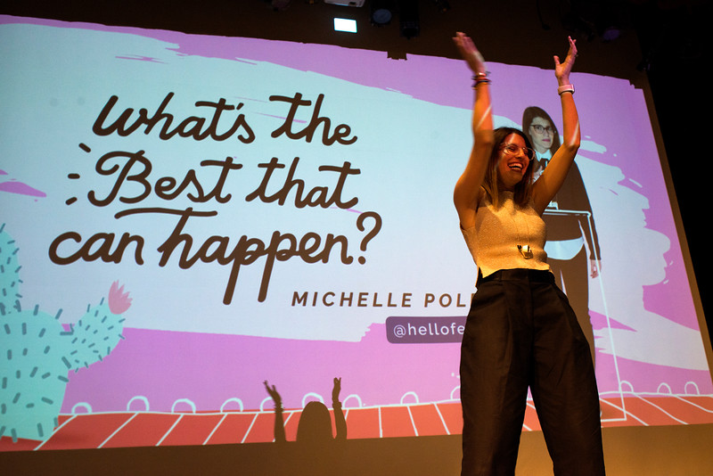 """LANCASTER, OHIO   MARCH 23, 2018: Michelle Poler, founder of Hello Fears, dances in front of the crowd as she takes the stage in the Wagner Theatre as one of the keynote speakers during the Celebrate Women Conference 2018, themed """"Recognizing Our Superpowers"""" on March 23, 2018 at Ohio University Lancaster in Lancaster, Ohio.  Ty Wright photo"""