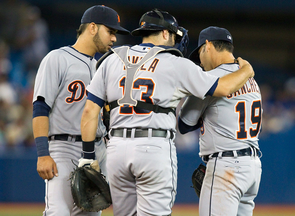 . Detroit Tigers catcher Alex Avila and Nick Castellanos talk to pitcher Anibal Sanchez, right, on the mound as he favors his pitching arm during the fifth inning of a baseball game, Friday, Aug. 8, 2014 in Toronto. (AP Photo/The Canadian Press, Fred Thornhill)