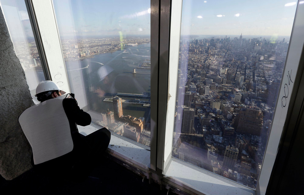 . A member of the media takes a photograph of the Manhattan skyline from the unfinished observation deck on the 100th floor of the One World Trade Center building, under construction in New York, Tuesday, April 2, 2013. The observation deck will occupy the tower\'s 100th through 102nd floors. Elevators will whisk visitors to the top in just one minute but the experience of visiting the attraction will take an hour. (AP Photo/Richard Drew)
