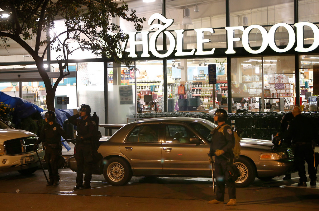 . Police stand guard in front of the Whole Foods on Telegraph Avenue in Berkeley, Calif., on Monday morning, Dec. 8, 2014, after it was vandalized during a second consecutive night of local unrest over the killings of two unarmed black men by police in Ferguson, Mo., and New York. (Karl Mondon/Bay Area News Group)