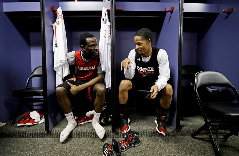 . Louisville\'s Michael Baffour, left, and Jordan Bond chat in the locker room before practice for their NCAA Final Four tournament college basketball game Sunday, April 7, 2013, in Atlanta. Louisville plays Michigan in the championship game on Monday. (AP Photo/Charlie Neibergall)
