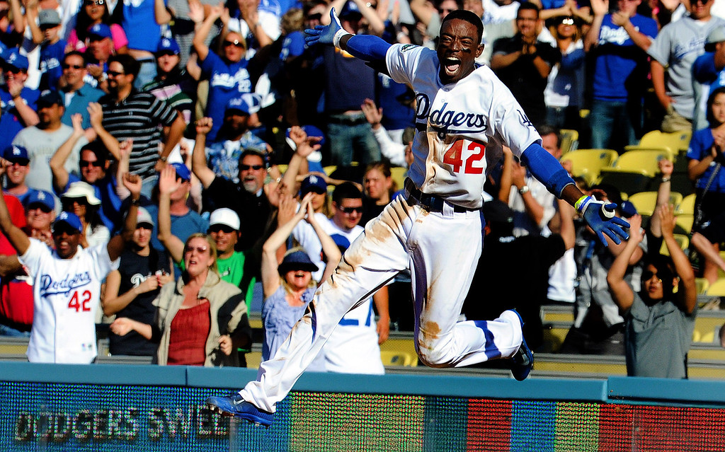 ". Los Angeles Dodgers\' Dee Gordon reacts after a game winning single with bases loaded as Juan Rivera scores to beat the San Diego Padres 5-4 in the ninth inning of a baseball game in Los Angeles on Sunday, April 15, 2012.  Jackie Robinson\'s Nephew William Robinson, left, cheers while wearing the number ""42\"" jersey.  (Keith Birmingham/Pasadena Star-News)"