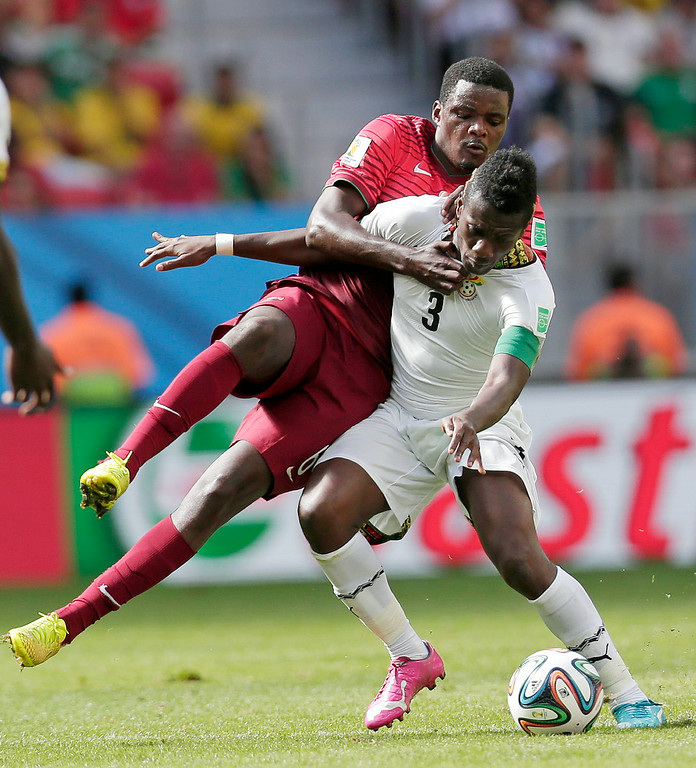 . Portugal\'s William Carvalho fights for the ball with Ghana\'s Asamoah Gyan during the group G World Cup soccer match between Portugal and Ghana at the Estadio Nacional in Brasilia, Brazil, Thursday, June 26, 2014. (AP Photo/Marcio Jose Sanchez)