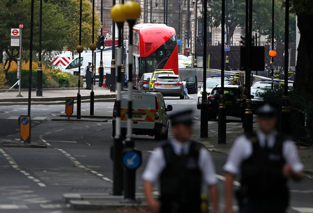 . A forensics officers prepares to examine the scene near a car that crashed into security barriers outside the Houses of Parliament to the right of a bus in London, Tuesday, Aug. 14, 2018. London police say that a car has crashed into barriers outside the Houses of Parliament and that there are a number of injured. (AP Photo/Alastair Grant)