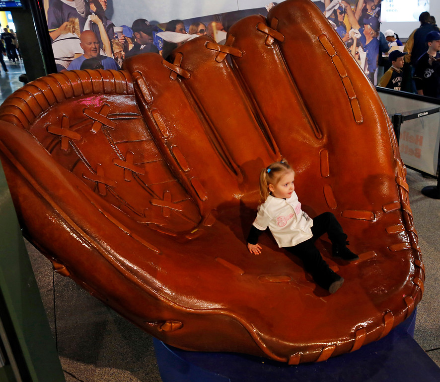 . Lilly Nowakowski, 2, slides down a big glove before the opening day baseball game between the Milwaukee Brewers and Atlanta Braves at Miller Park, Monday, March 31, 2014, in Milwaukee. (AP Photo/Jeffrey Phelps)