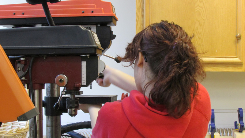 Savannah lines up her drill bit before starting a task.