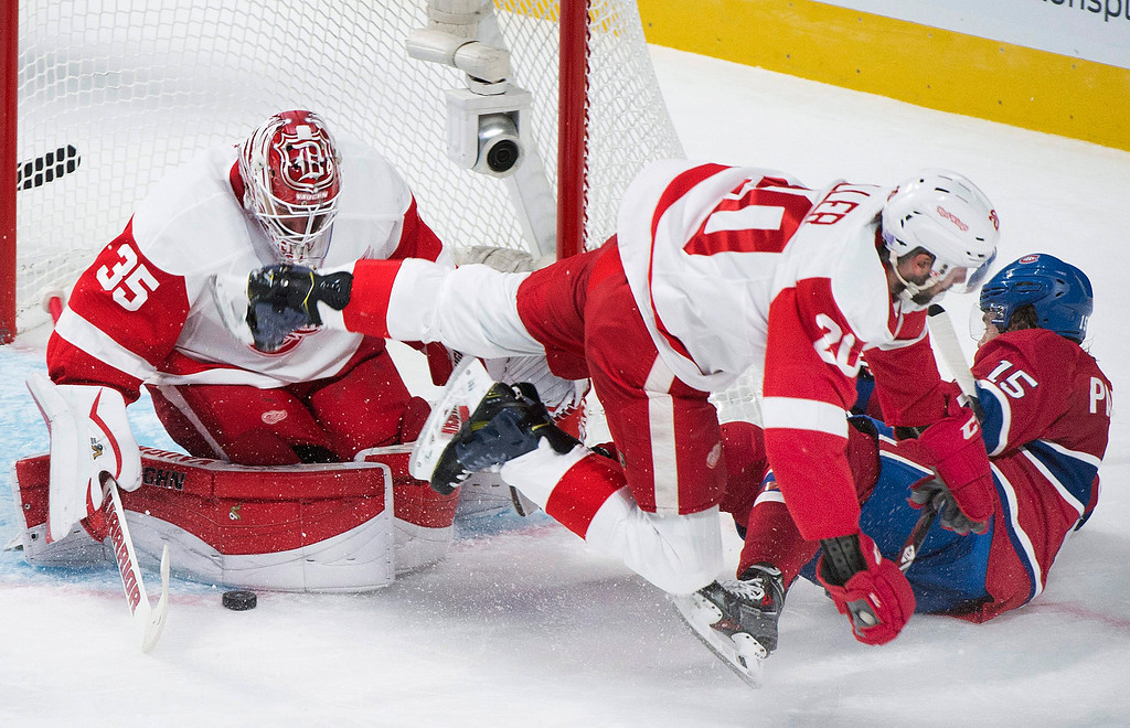 . Detroit Red Wings goaltender Jimmy Howard, left, makes a save against Montreal Canadiens\' Pierre-Alexandre Parenteau, right, as Red Wings\' Drew Miller (20) defends during second period NHL hockey action in Montreal, Tuesday, Oct. 21, 2104. (AP Photo/The Canadian Press, Graham Hughes)