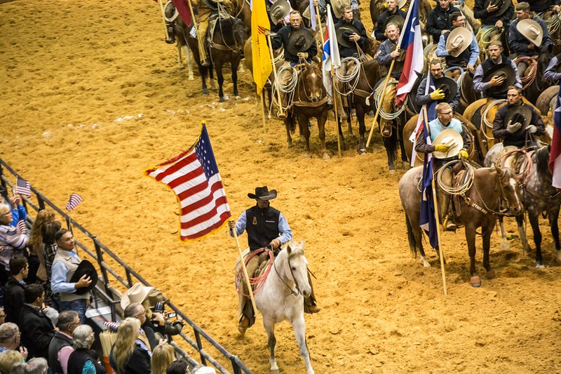 Cowboy riding with the American flag at a Texas rodeo