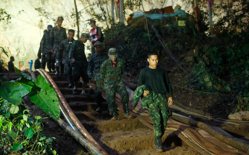 . Rescuers make their way down at the entrance to a cave complex where 12 boys and their soccer coach went missing, in Mae Sai, Chiang Rai province, in northern Thailand, Monday, July 2, 2018. Rescue divers are advancing in the main passageway inside the flooded cave in northern Thailand where the boys and their coach have been missing more than a week. (AP Photo/Sakchai Lalit)