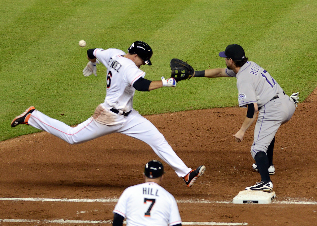 . MIAMI, FL - AUGUST 24: Pitch Jose Fernandez #16 of the Miami Marlins tries to beat out a bunt in front of first baseman Todd Helton #17 of the Colorado Rockies at Marlins Park on August 24, 2013 in Miami, Florida.  (Photo by Jason Arnold/Getty Images)