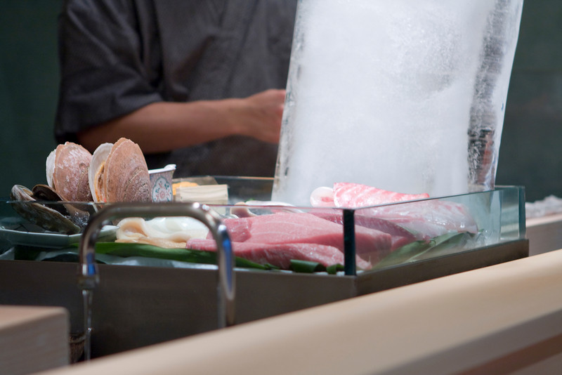 The tray of raw fish.  The big hunk of ice got smaller as the night wore on.  by the end of the night, it was a fairly thin sheet of ice.  You can see the live scallop.  The container on the right of the scallop contains cut up raw shrimp (amaebi).  You can see the toro and red snapper on the bottom.