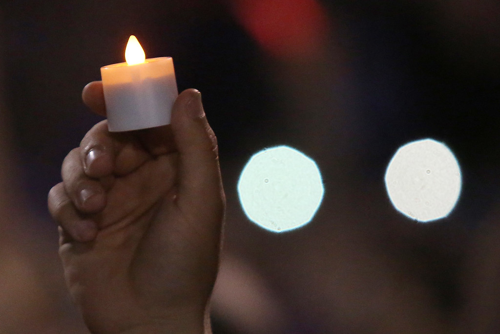 . A man holds a candle during a vigil and memorial gathering at the Prescott High School in Prescott, Arizona on July 2, 2013. TAFP PHOTO / KRISTA Kennell/AFP/Getty Images