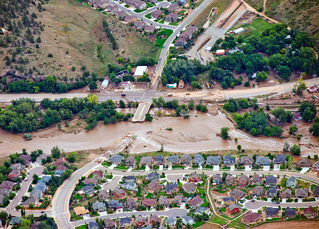 . A residential neighborhood and a connecting road in Lyons, Colo., are cut in two by flood waters as flooding continues to devastate the Front Range and thousands are forced to evacuate with an unconfirmed number of structures destroyed Friday, Sept. 13, 2013. (AP Photo/John Wark)