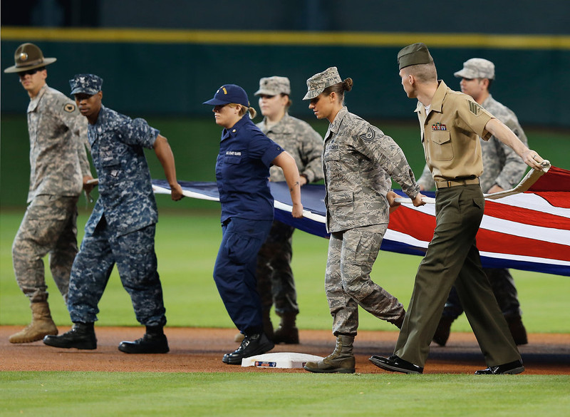 . Members of the military carry an American flag onto the field before the start of the game between the Colorado Rockies and the Houston Astros at Minute Maid Park on May 27, 2013 in Houston, Texas.  (Photo by Scott Halleran/Getty Images)
