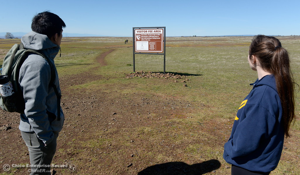 . Cliff Chao left and Holly Shafer of Davis look at the fee sign as they get ready to enjoy a stroll through the wildflowers  just beginning to bloom on Table Mountain Monday March 5, 2018. Hikers 16-years or older are now required to have a Lands Pass or valid hunting or fishing license. (Bill Husa -- Enterprise-Record)