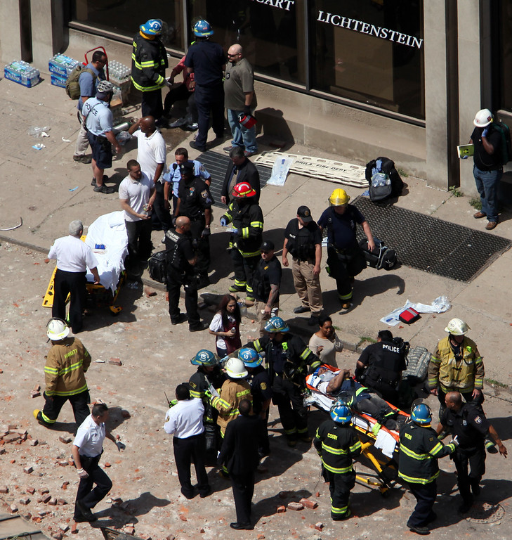 . Rescue personnel evacuate an injured person from the scene of a building collapse in downtown Philadelphia, Wednesday, June 5, 2013.   (AP Photo/Jacqueline Larma)
