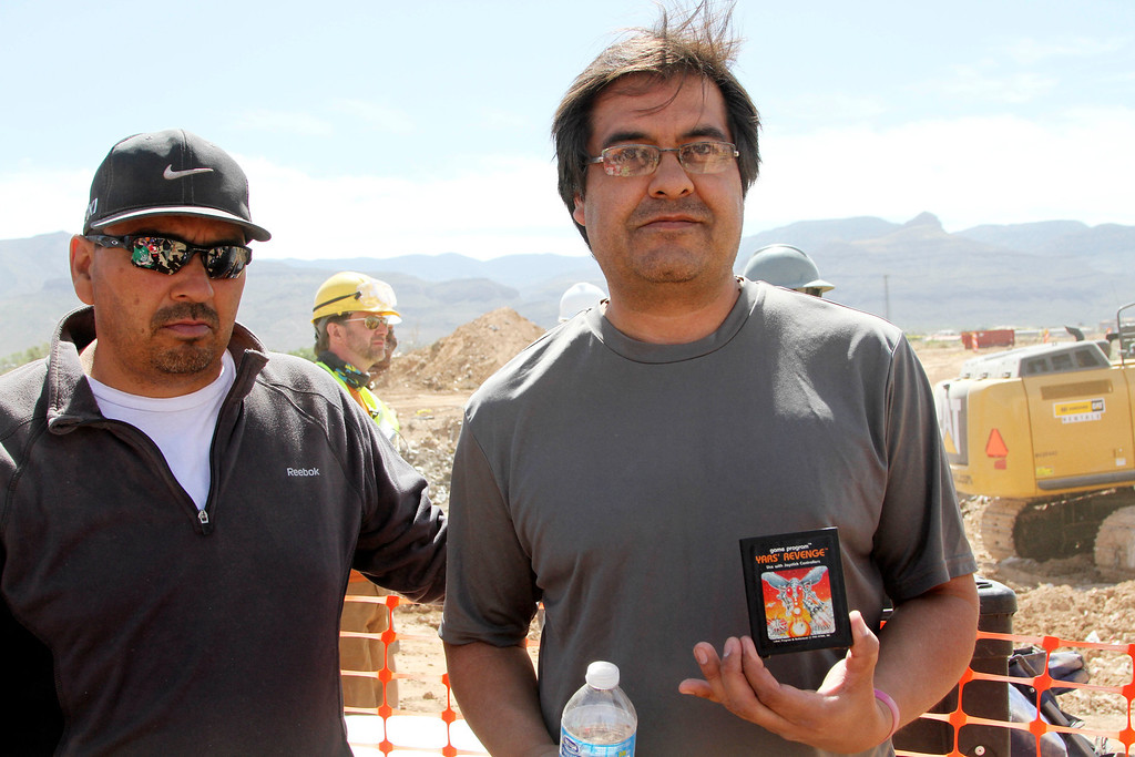 . Alamogordo residents Armando Ortega, left, and Raul Ruiz pose for a photograph with a cartridge they found buried in a landfill in Alamogordo, N.M., Saturday, April 26, 2014. Producers of a documentary dug in an southeastern New Mexico landfill in search of millions of cartridges of the Atari \'E.T. the Extra-Terrestrial\' game that has been called the worst game in the history of video gaming and were buried there in 1983. (AP Photo/Juan Carlos Llorca)