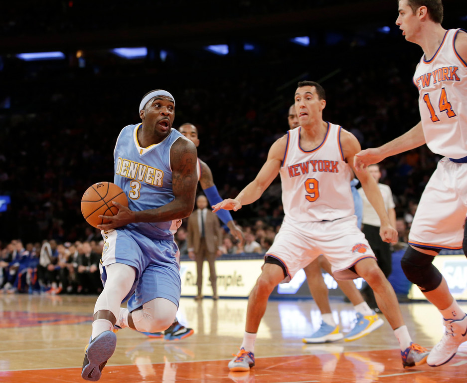 . Denver Nuggets guard Ty Lawson (3) drives into the paint as New York Knicks guard Pablo Prigioni (9) and center Jason Smith (14) look on in the first half of an NBA basketball game in New York, Sunday, Nov. 16, 2014. (AP Photo/Kathy Willens)