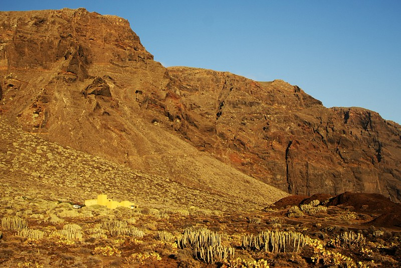 Osamělý žlutý dům pod útesy Los Gigantes