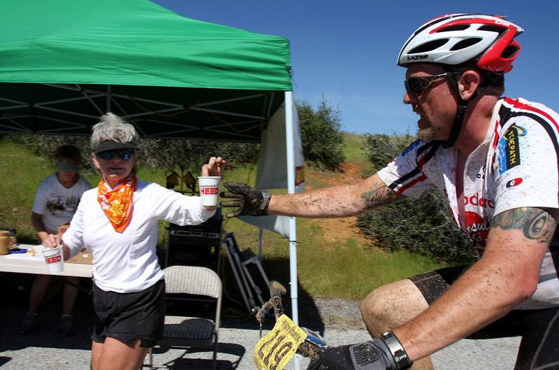 Aid station worker hands water to Alan Lang.