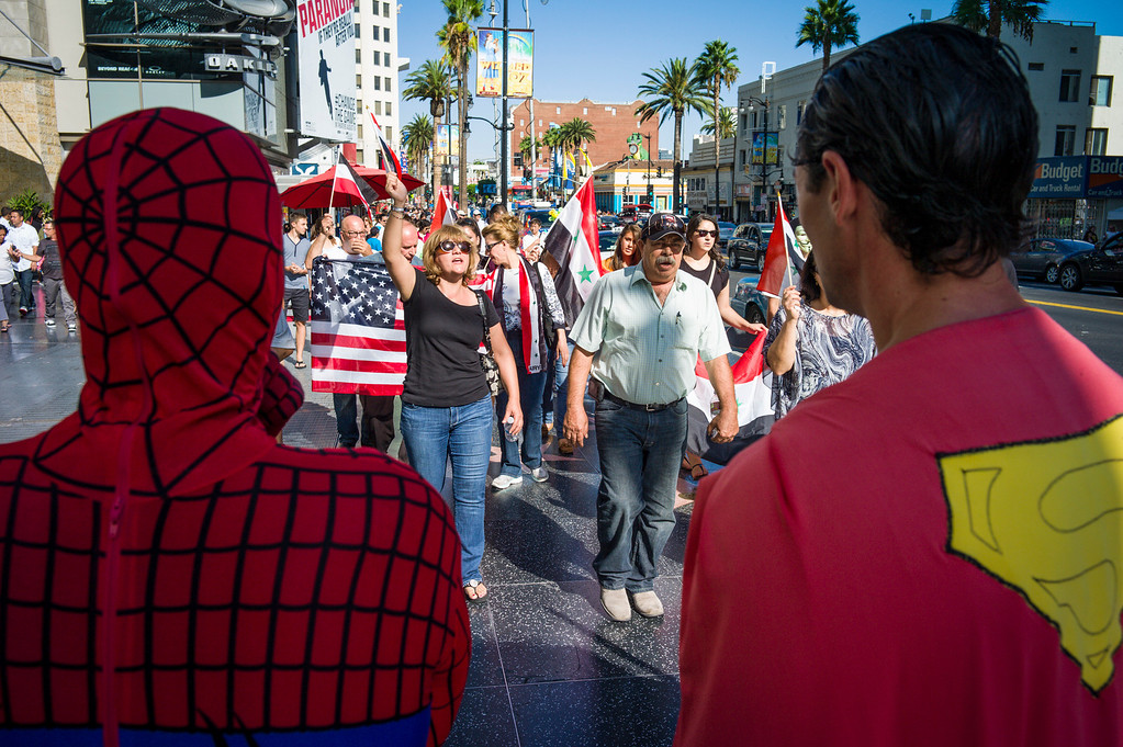 . Spiderman and superman watch as 200 protestors approach them along Hollywood blvd to protest the possible US involvement in Syria Sunday, September 8, 2013.  The protest brought out police in riot gear to try and contain the protest to the sidewalks.    ( Photo by David Crane/Los Angeles Daily News )