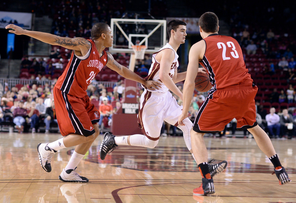 . DENVER, CO. - FEBRUARY 8, 2014: Denver junior guard Brett Olson (23) crossed the key in front of Coyotes defenders Karim Rowson (24) and tyler Flack (23) in the second half. The University of Denver defeated South Dakota 75-67 Saturday evening, February 8, 2014. Photo By Karl Gehring/The Denver Post