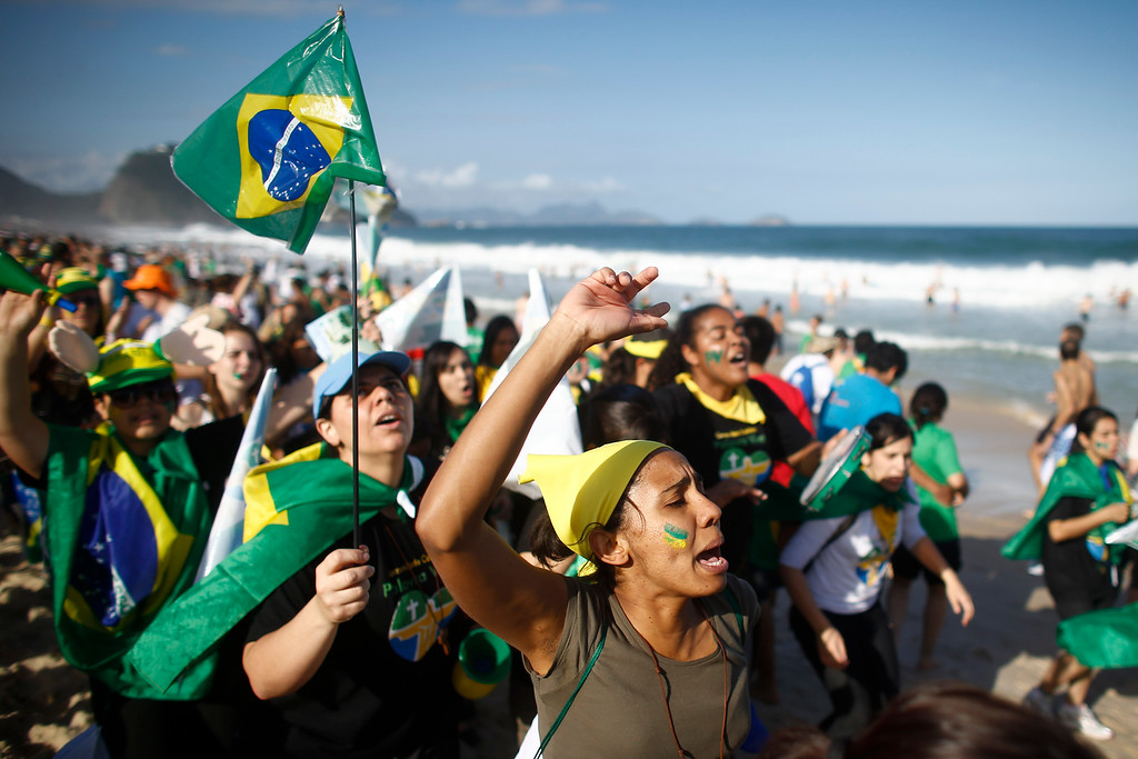 . Pilgrims carrying a Brazilian flag sing on Copacabana beach in Rio de Janeiro, Brazil, Saturday, July 27, 2013. Pope Francis will preside over an evening vigil service on Copacabana beach that is expected to draw more than 1 million young people. (AP Photo/Victor R. Caivano)