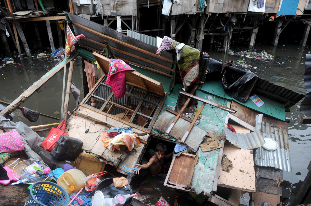 . A resident (bottom C) searches for salvageable materials in his destroyed home after it collapsed into a creek after a fire razed a slum area in Manila on July 24, 2013.  Almost 200 houses were destroyed, leaving 400 residents homeless, according to a local media report.   NOEL CELIS/AFP/Getty Images