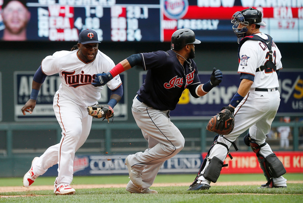 . Minnesota Twins third baseman Miguel Sano, left, chases Cleveland Indians\' Carlos Santana before tagging him out during a rundown in the eighth inning of the first baseball game of a doubleheader, Thursday, Aug. 17, 2017, in Minneapolis. The Indians won 9-3. (AP Photo/Jim Mone)