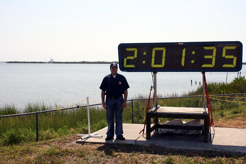 Craig with the countdown clock at T minus 2 hours, 1 minute, and 35 seconds to liftoff, with Space Shuttle Atlantis on Launch Pad 39-A in the background