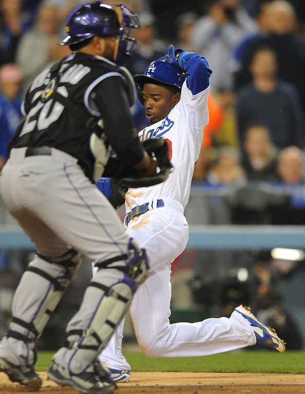 . The Dodgers\' Dee Gordon slides home past Rockies catcher Wilin Rosario and scores from second on a hit by Yasiel Puig in the third inning, Friday, April 25, 2014, at Dodger Stadium. (Photo by Michael Owen Baker/L.A. Daily News)