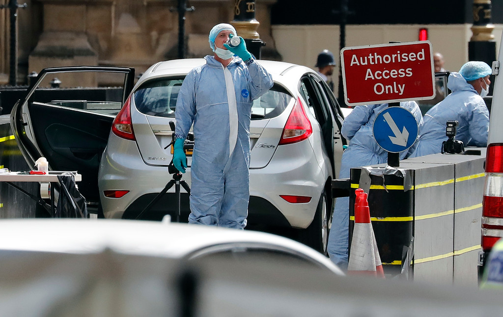 . Forensics officers work on the car that crashed into security barriers outside the Houses of Parliament to the right of a bus in London, Tuesday, Aug. 14, 2018. Authorities said in a statement Tuesday that a man in his 20s was arrested on suspicion of terrorist offenses after a silver Ford Fiesta collided with a number of cyclists and pedestrians before crashing into the barriers during the morning rush hour. (AP Photo/Frank Augstein)