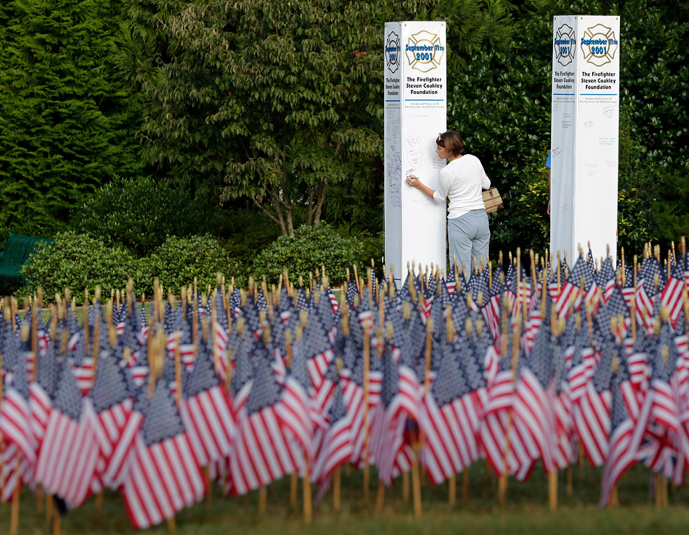 . A woman writes on a replica of a twin trade towers behind a sea of American flags during a memorial in Matthews, N.C., on the 13th anniversary of the Sept. 11, 2001 attacks, Thursday, Sept. 11, 2014. The 2,997 American flags are displayed for each person lost on Sept. 11, 2001. (AP Photo/Chuck Burton)