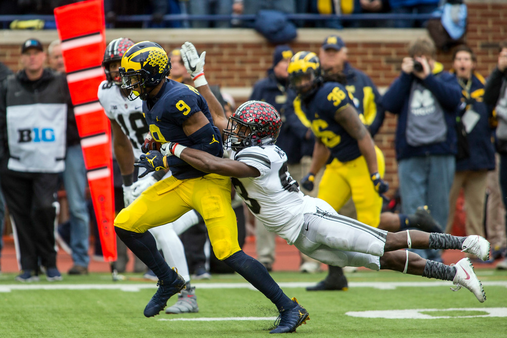 . Michigan wide receiver Donovan Peoples-Jones (9) returns a punt and attempts to break a tackle from Ohio State wide receiver Terry McLaurin (83), in the first quarter of an NCAA college football game in Ann Arbor, Mich., Saturday, Nov. 25, 2017. (AP Photo/Tony Ding)