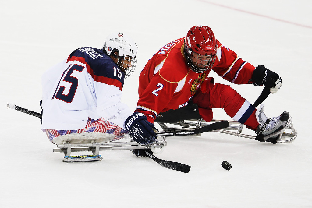 . Nikko Landeros of the USA competes with Aleksei Lysov of Russia during the ice sledge hockey gold medal game between the Russian Federation and the United States of America at the Shayba Arena during day eight of the 2014 Paralympic Winter Games on March 15, 2014 in Sochi, Russia.  (Photo by Hannah Peters/Getty Images)