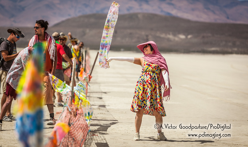 At one of the farthese points within Burning Man, an art car set up a tie dye actitvity. Stepping outside the fence, a woman shows off her new scarf.